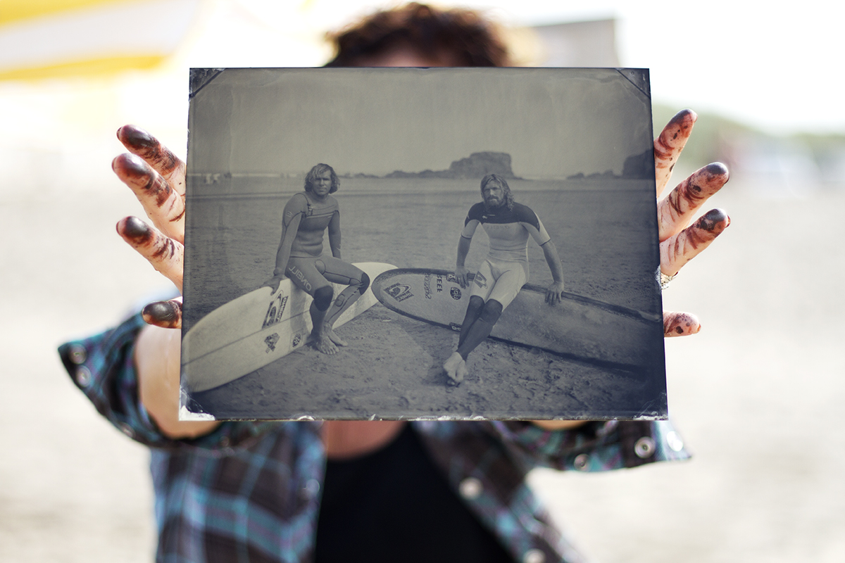 holding up a wet plate tin type image of two surfers