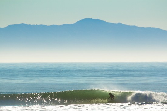 Surfer in a backlit barrel at Rincon in California shot by Michael Kew