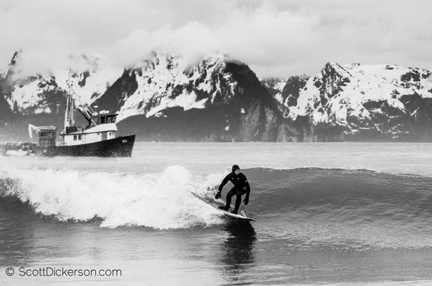 Michael Kew surfing in Alaska with a fishing boat and snowy mountains in the background