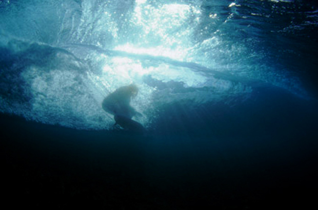 underwater image of michael kew seen surfing through the back of the barrel