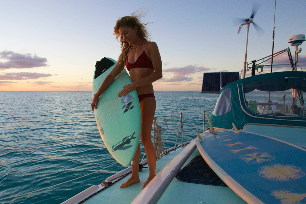 surfer liz clark holding her surfboard on the deck of her boat swell