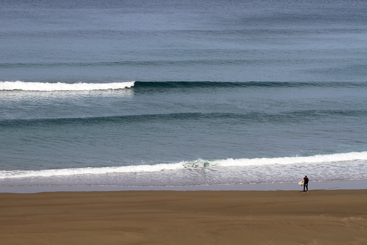 a surfer walks back up the beach whilst a wave breaks behind him