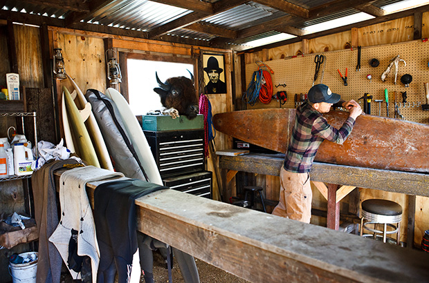 Chris Malloy restoring a hollow wooden cigar-box style paddle board in the workshop in his barn, surrounded by tools and surfboards.  Photographed by Jeff Johnson for Patagonia Inc.