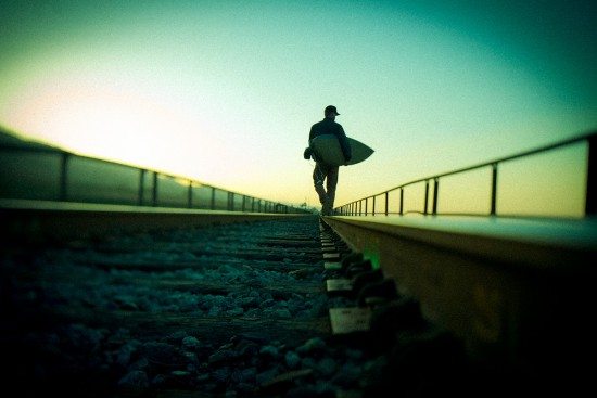 Chris Malloy walking the train tracks at dawn near home in California, photographed for Patagonia by Tim Davis