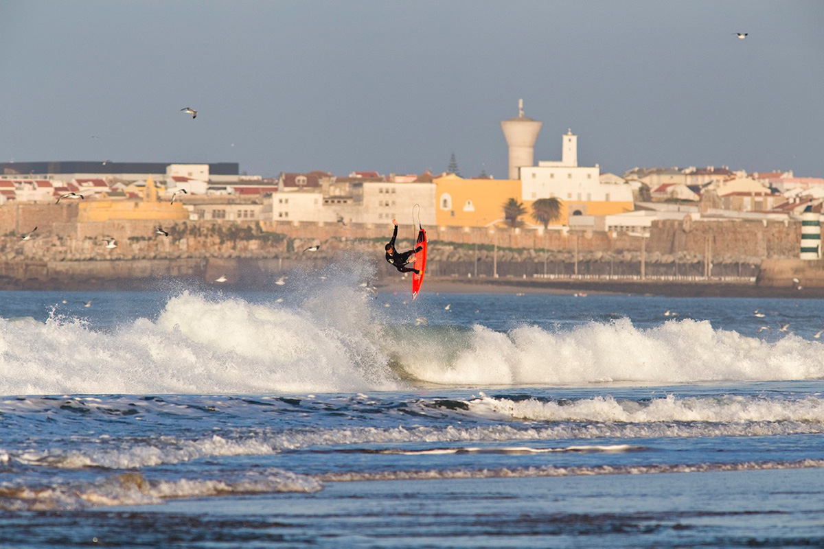 surfer william aliotti performing an alley-oop at supertubes in peniche, portugal. Photograph by Greg Martin.