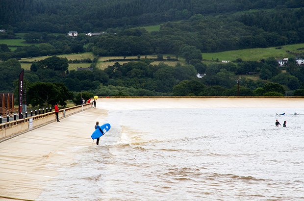 a surfer holding a soft blue beginners board waiting to enter the water to ride a wave at surf snowdonia