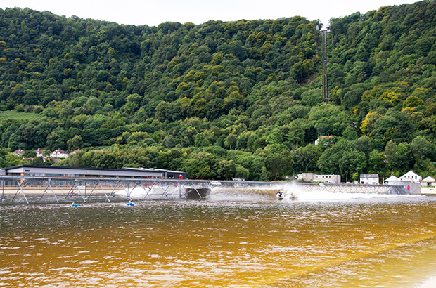 a surfer bottom turning on a right hand wave at the surf snowdonia wave garden in wales