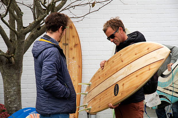 3 times world surfing champion tom curren inspecting a wooden surfboard shaped by james otter
