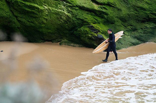 Matias Alcalde from Lobos Por Siempre getting out of the sea after a surf on an otter wooden surfboard