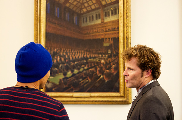 big wave surfer ramon navarro and dr chad nelson of the surfrider foundation talking in front of a painting in the houses of parliament in london, england