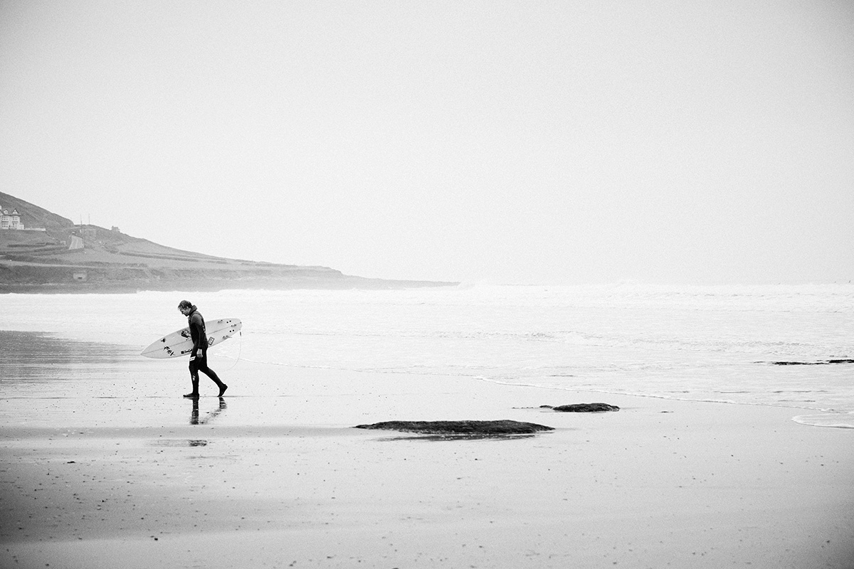 big wave surfer andrew cotton walking back up the beach after a surf