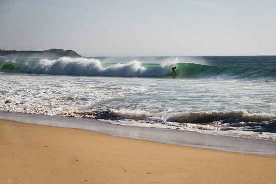 a surfer getting barreled at supertubos in peniche