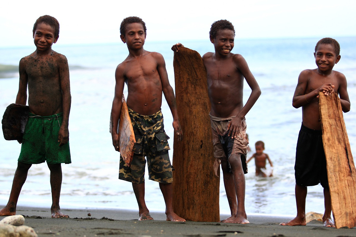 young children in papua new guinea pose with their splinter surf boards carved from local trees or broken canoes