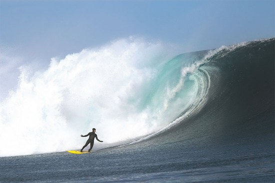 Ramon Navarro in a relaxed pose at the bottom of a big wave, surfing in a patagonia wetsuit