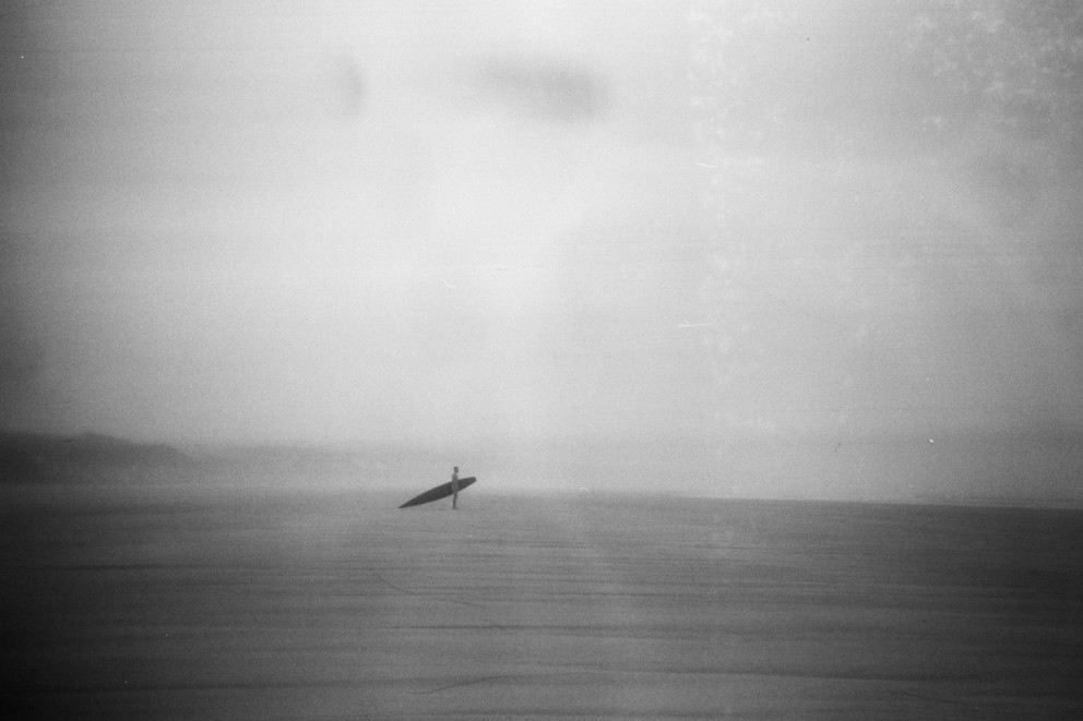 a lone surfer holding a replica 1920s cigar box wooden surfboard designed by tom blake, photographed on a vintage box brownie camera