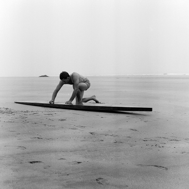 surfer using a candle to wax the deck of a replica tom blake style hollow wooden surfboard, photographed on a vintage tlr camera by mat arney