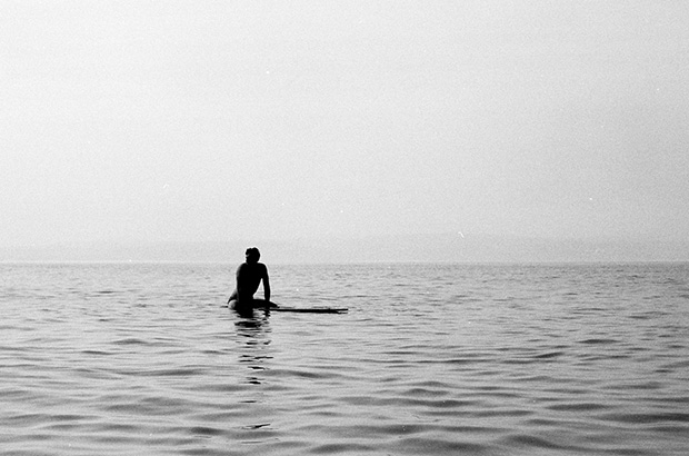 black and white photograph of surfer sitting on hollow tom blake style paddle board waiting for a wave, photographed from the water by mat arney
