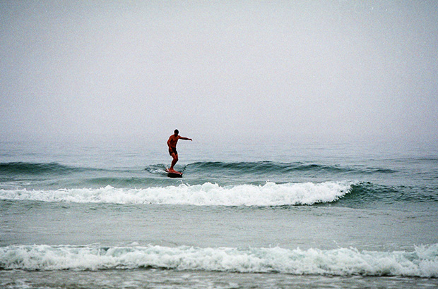 surfer wearing vintage navy seals swim shorts surfing in trim along a small left hand wave on a replica tom blake style hollow wooden surfboard called a cigar box