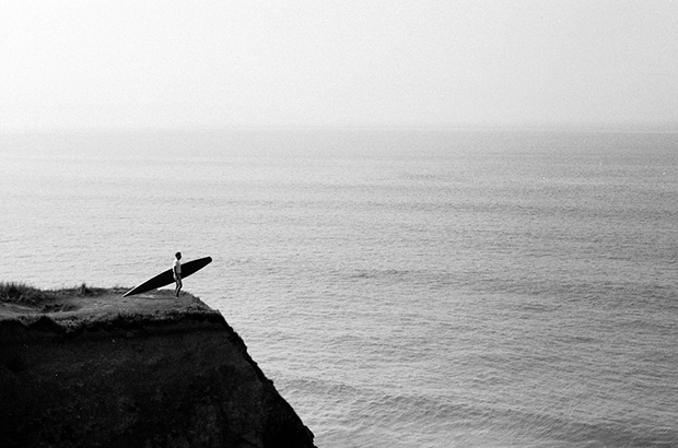 black and white photograph of surfer stood on cliff bluff overlooking sea holding a replica tom blake style hollow wooden surfboard