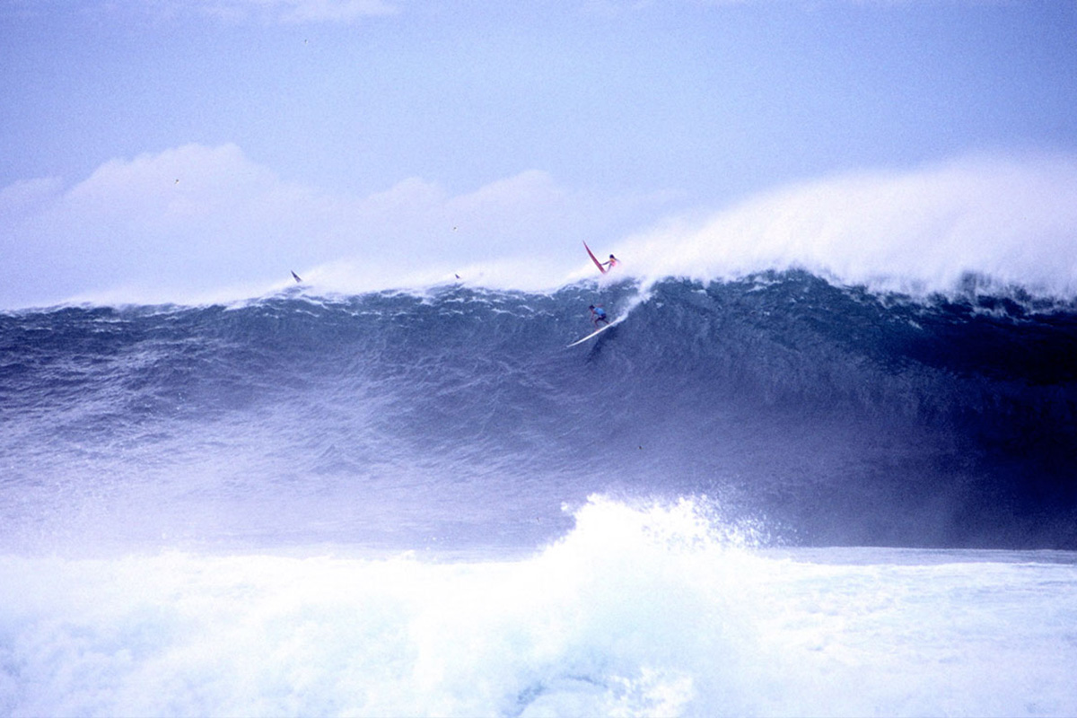 brock little air dropping into a huge wave during the 1990 quiksilver in memory of eddie aikau, photographed by buzzy kerbox
