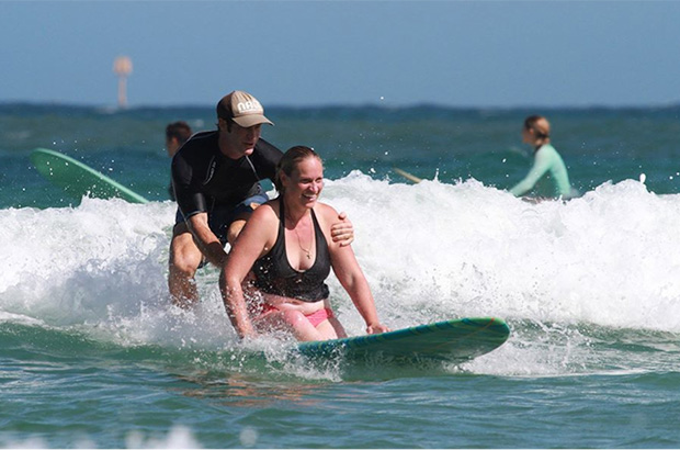 tandem surfer fred branger of nalu association riding a wave with an amputee friend