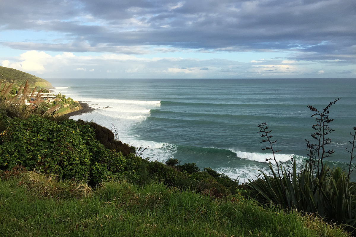 waves peeling down the left hand point break at whale bay in raglan, new zealand