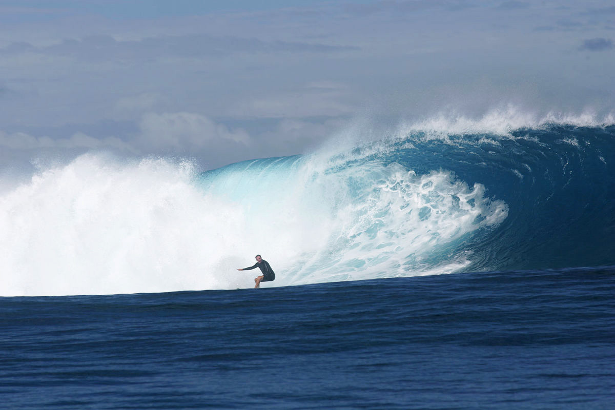 journalist and author william finnegan surfing a large wave at cloudbreak off the island of tavarua, fiji, in 2005