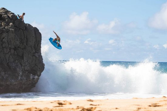 jamie o'brien jumping into the surf on a catch surf black ball beater surfboard at waimea