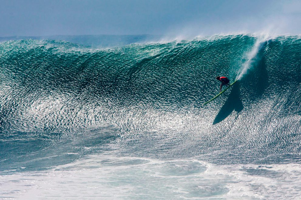 john john florence dropping into a big wave at the 2016 quiksilver in memory of eddie aikau, photographed by tom servais for world surf league