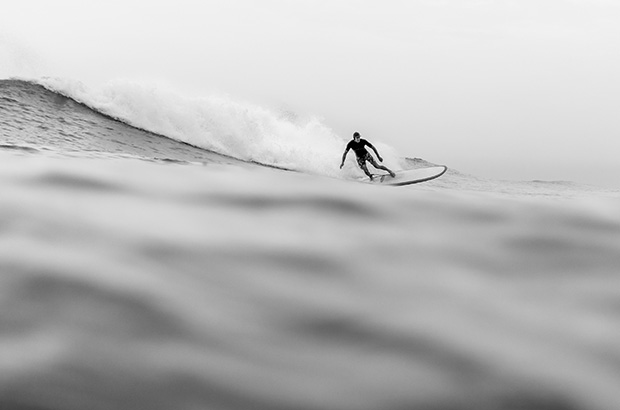 black and white image of a surfer dropping into a wave in India, photographed by Peter Chamberlain