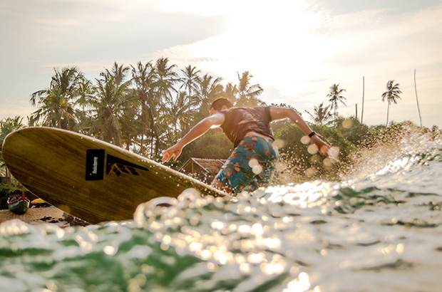 longboard surfer sam bleakley turning off the top in India at a palm tree backed beach, photographed by Peter Chamberlain