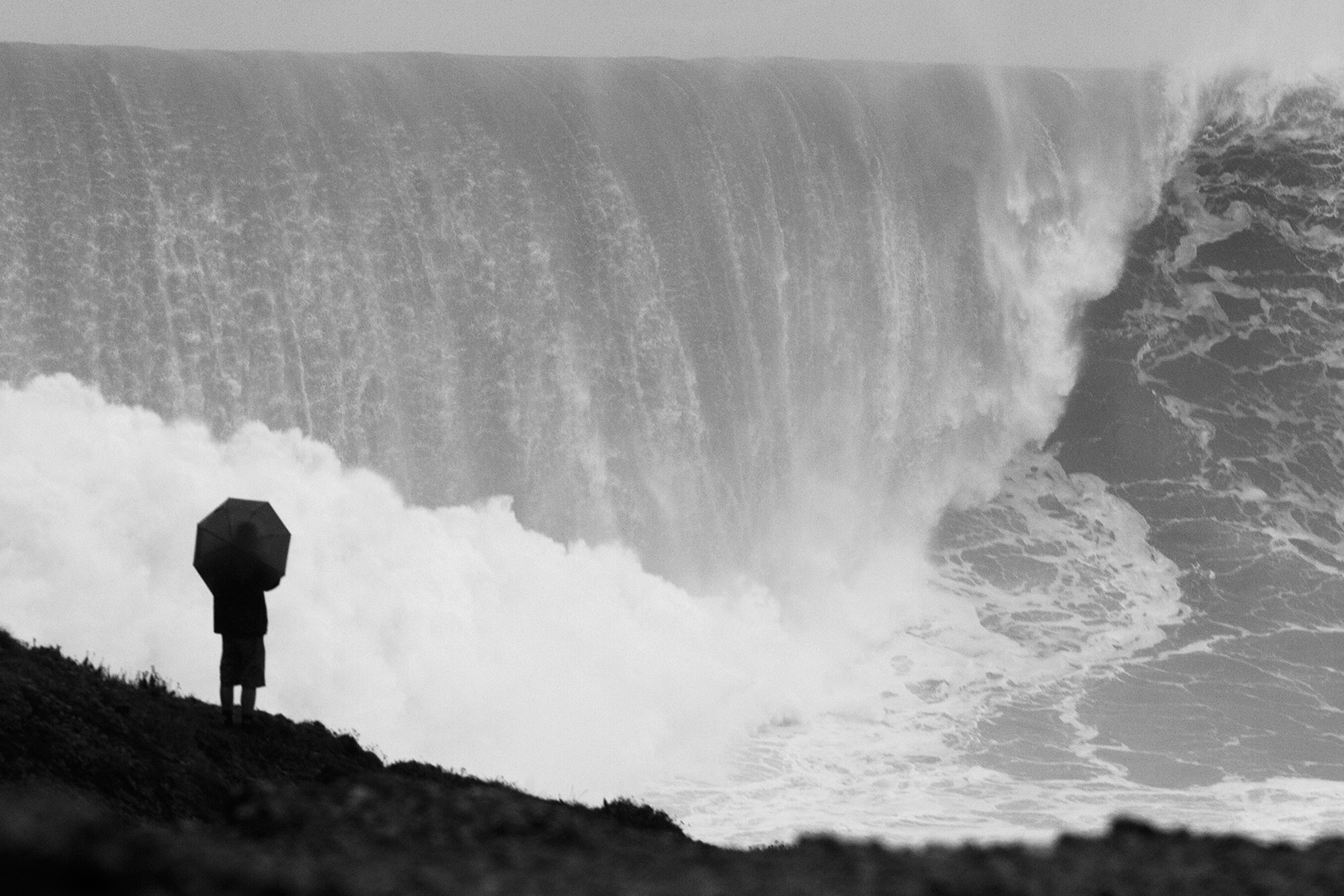 spectator holding an umbrella stood on the cliffs at nazare watching a giant wave break in front of them