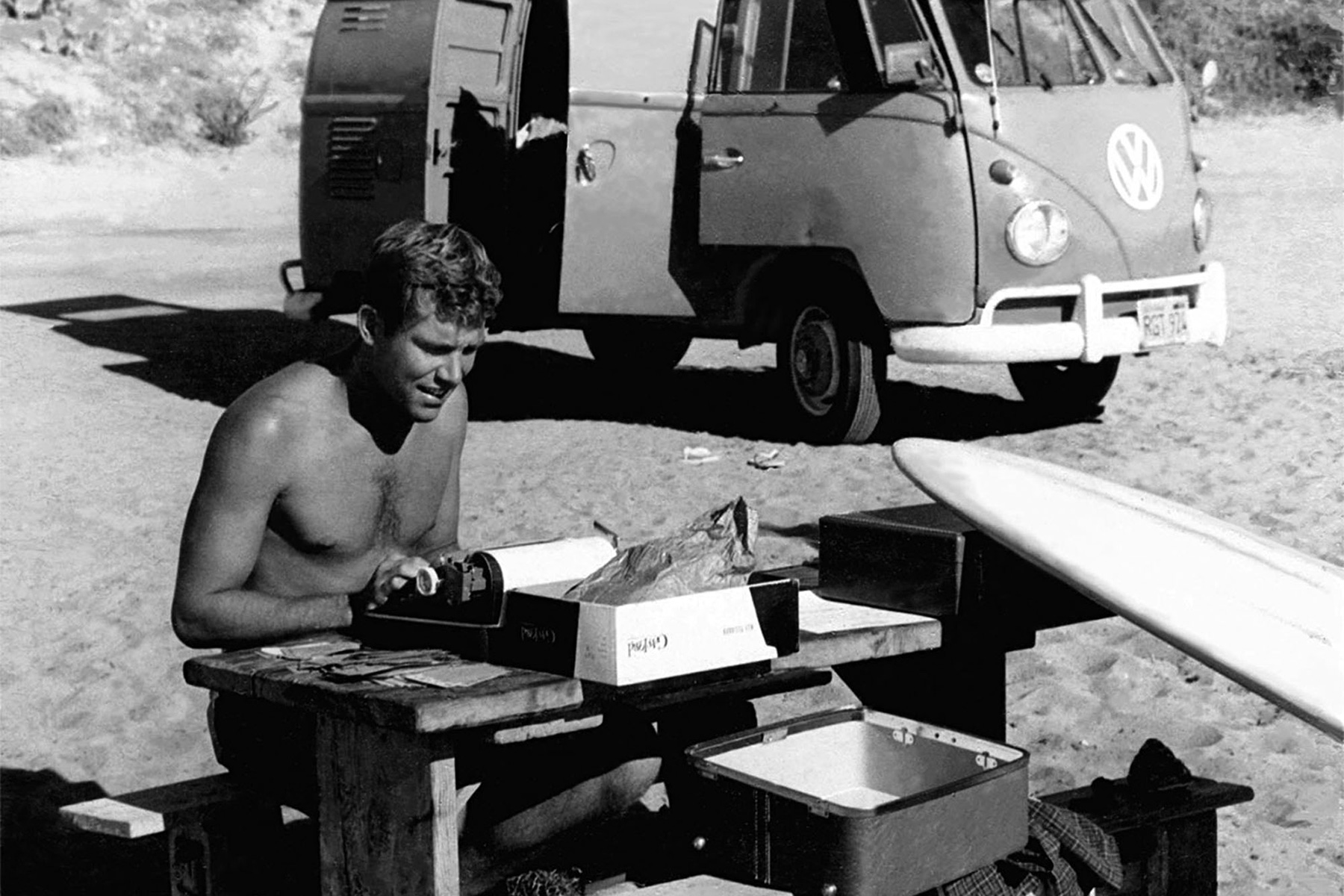 John Severson typing the first edition of Surfer Magazine at the beach next to his VW kombi van