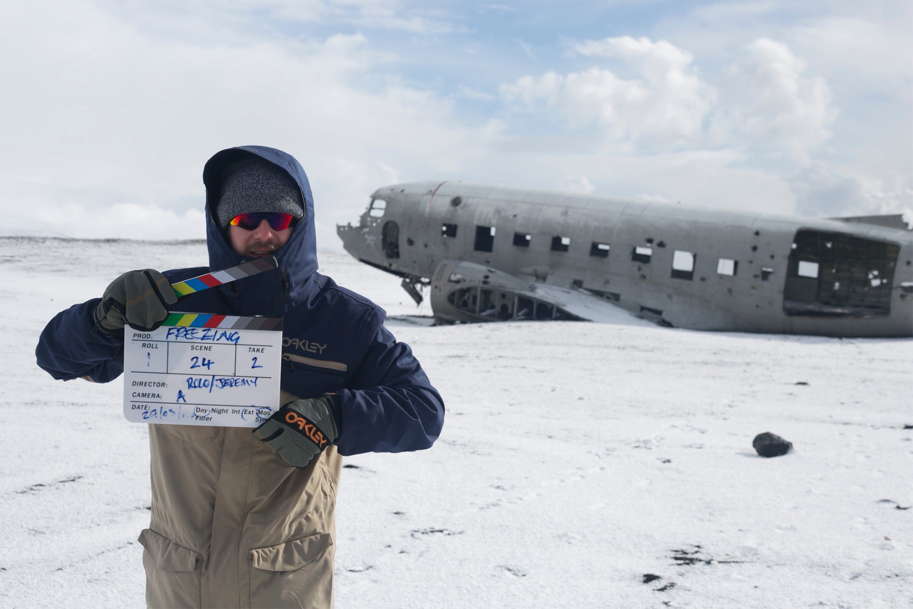 Surf filmmaker Rob Lockyear of Two Eyes Films on the set of Freezing in Iceland with a clapperboard in front of wrecked plane in snowfield