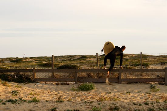 surf simply coach harry knight jumping the fence to the beach in France for a dawn surf during a surf simply trip to hossegor