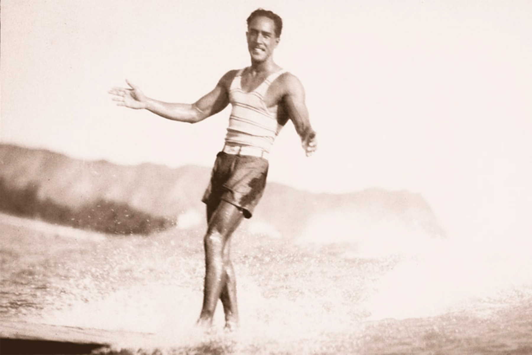 david kahanamoku surfing in front of diamond head, waikiki, in the 1930s