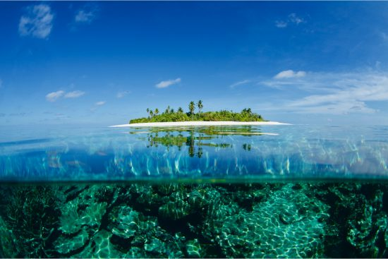 split over/underwater photo of a tropical atoll in the maldives photographed by Morgan Maassen