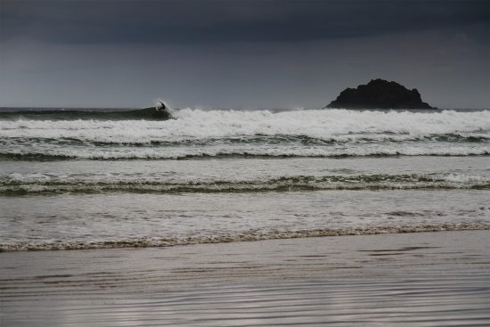 surfer performing an off-top on a wave in front of the island at Polzeath, Cornwall in southwest UK on a stormy day. Photograph by Mat Arney
