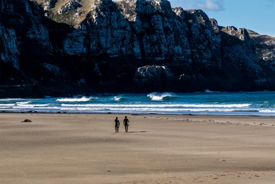 wo surfers walk along the beach towards a remote wave under towering cliffs at PK bay on new zealand's south island