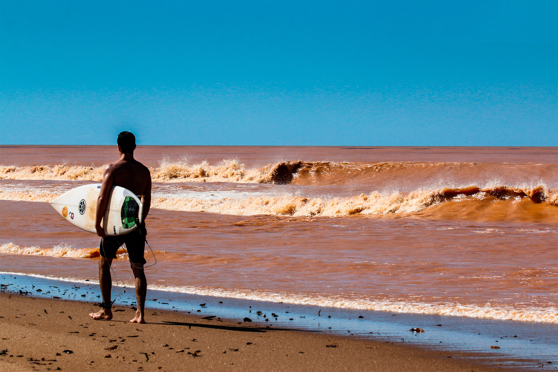 a surfer walking on the beach in regencia, brazil, where toxic mud pollutes the surf break