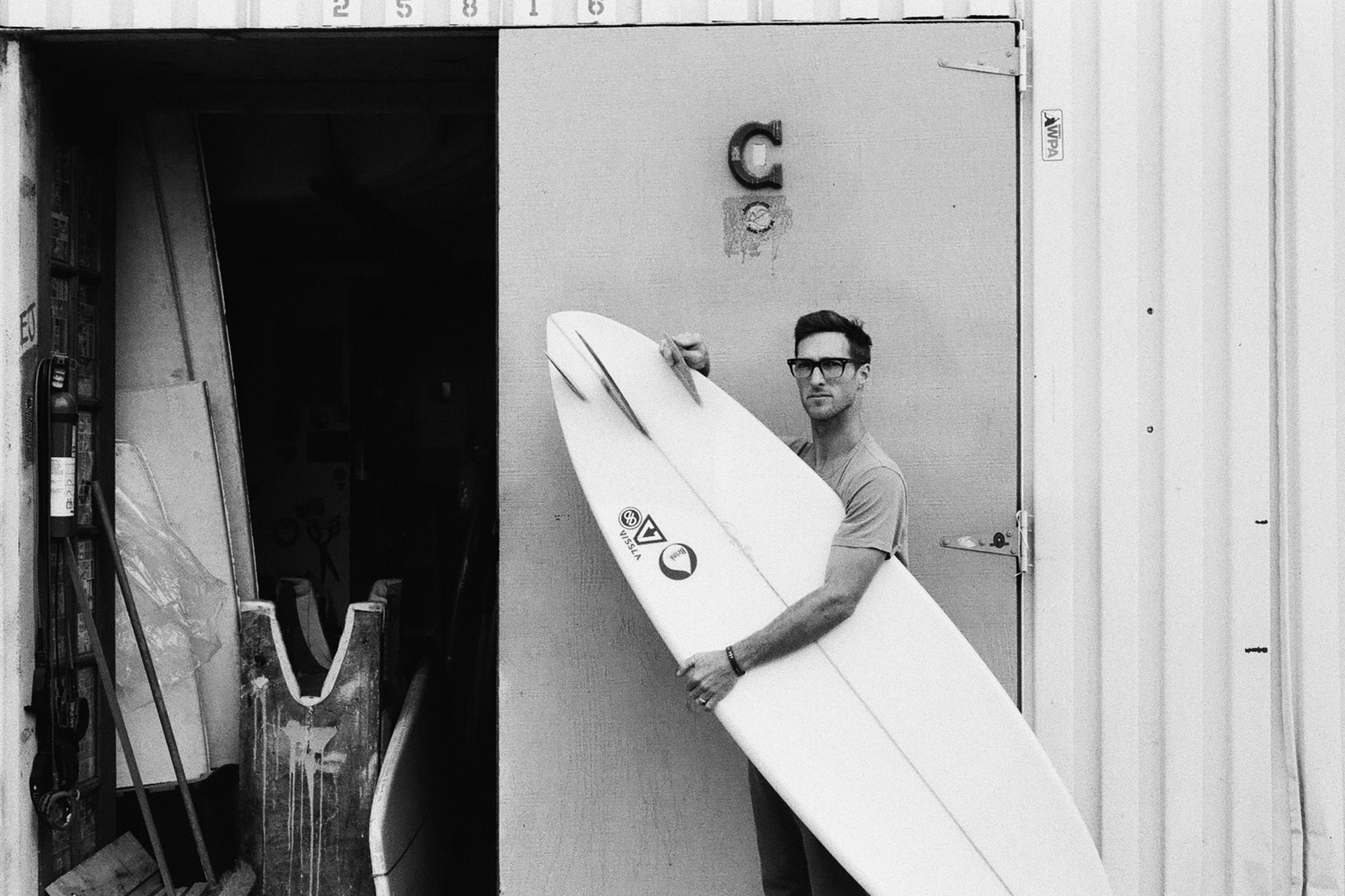 surfboard shaper donald brink outside his factory holding an asymmetrical surfboard