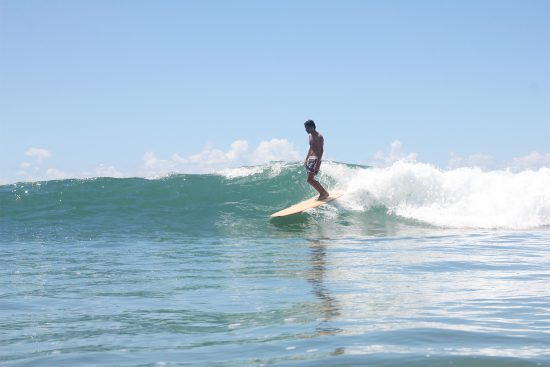 stylish surfer riding a wooden longboard shaped by filipe siebert