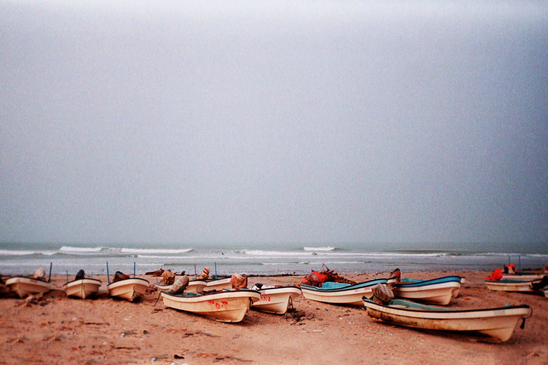 traditional fishing boats pulled up on a beach in oman, with waves breaking behind them