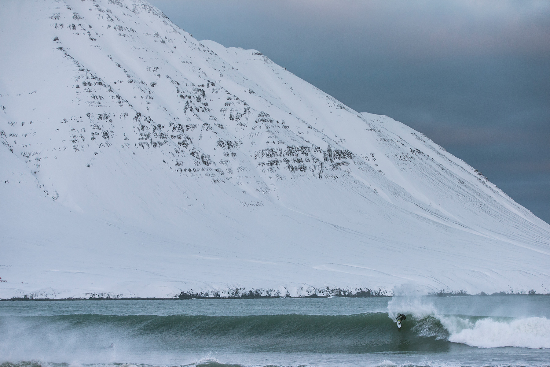 surfer turning on a wave in front of a snow covered mountain in iceland, photographed by elli thor magnussen