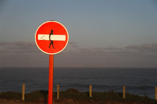 a no entry sign with a stencil graffiti of a surfer, and the sea in the background