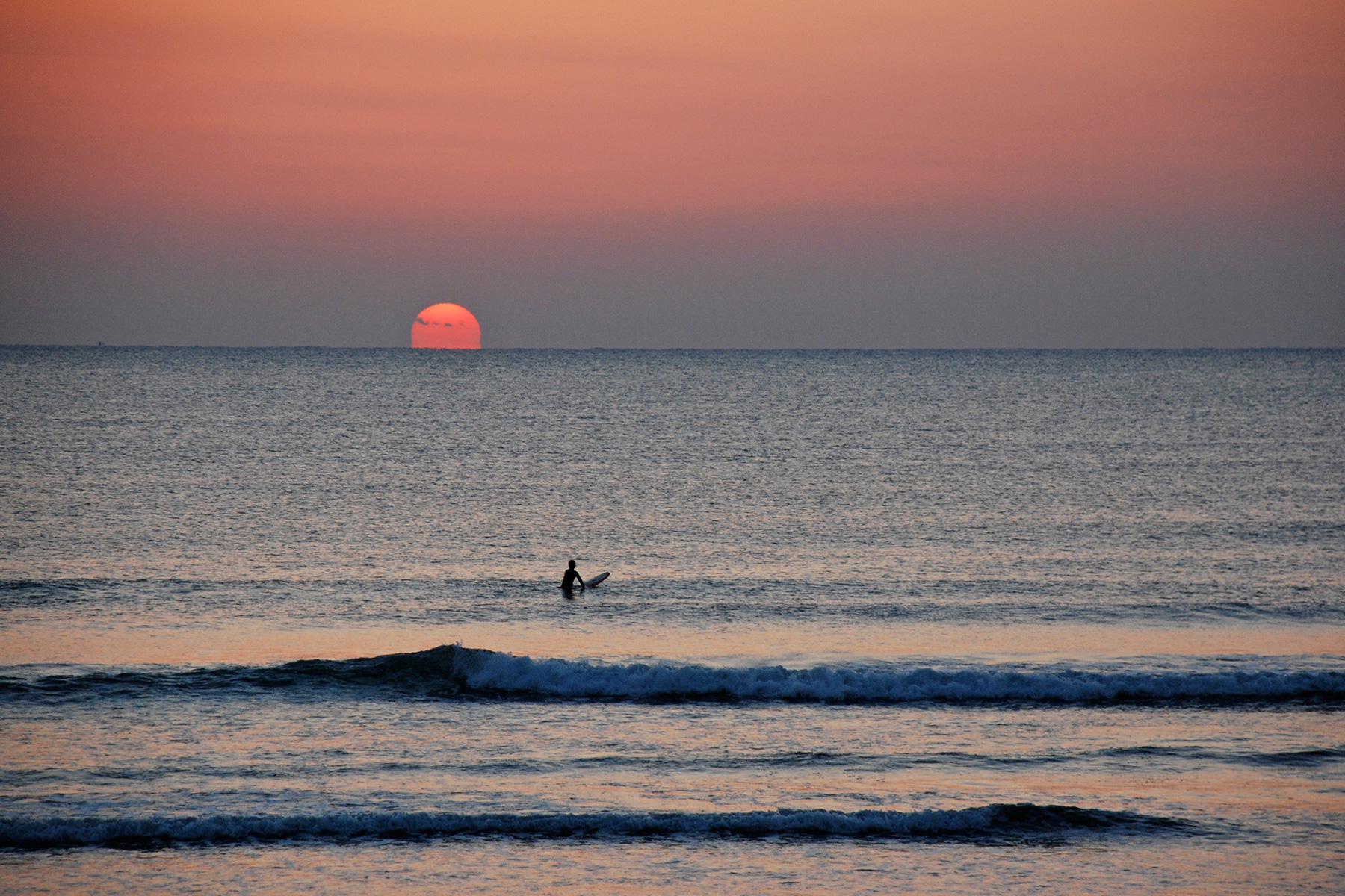 a surfer sits waiting for a wave in front of the rising sun in japan