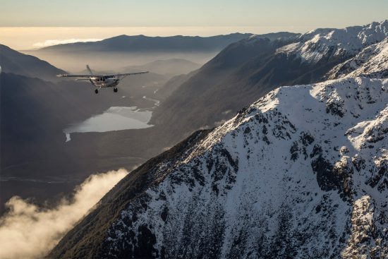 a light aircraft flies past snow covered mountains in new zealand's fiordland national park, photographed by dan kerins