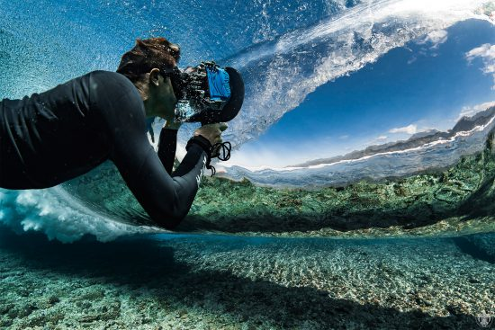 underwater photographer ben thouard at work beneath the surface n tahiti, taking a photo of the land through the back of a breaking wave