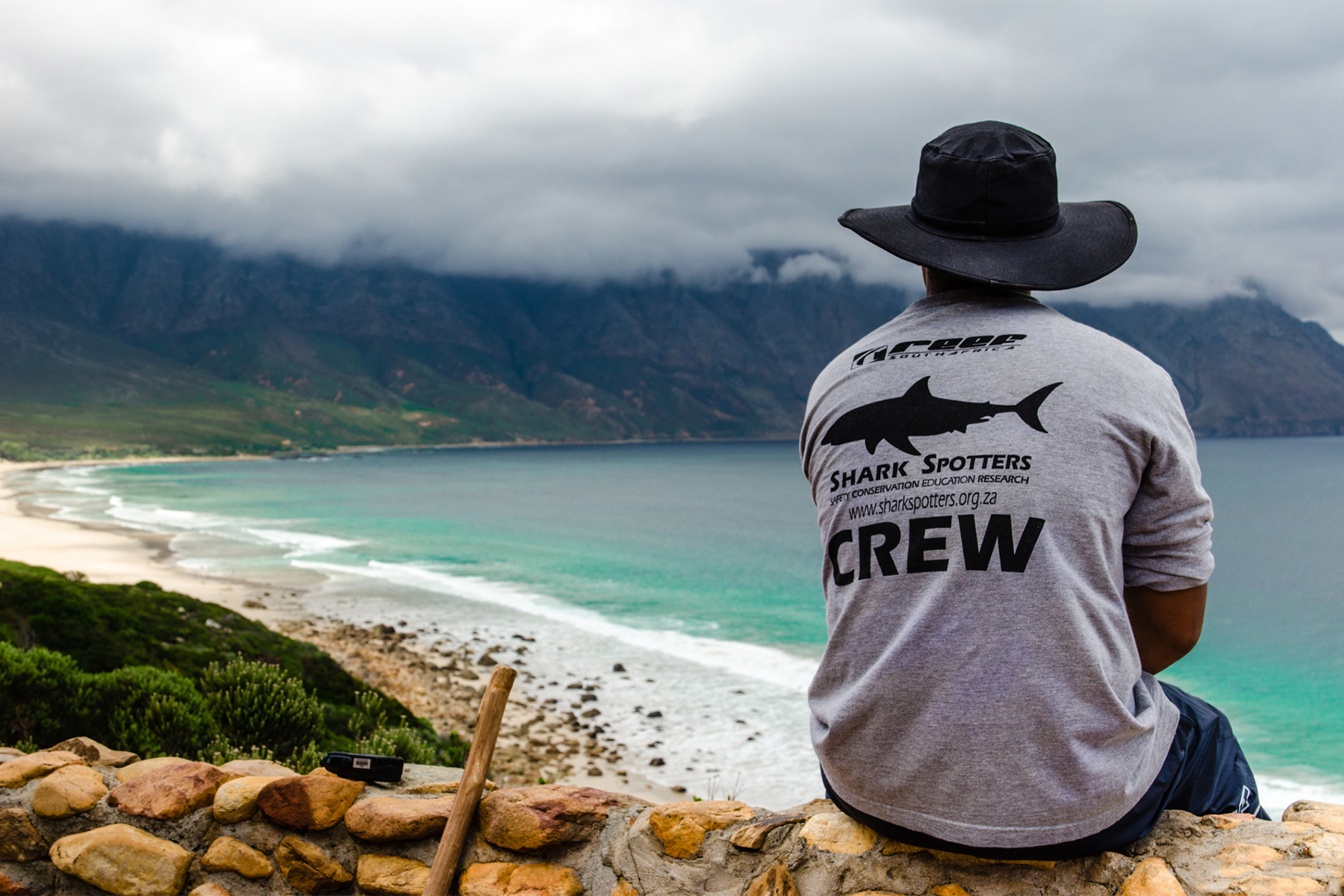 a memeber of cape town's shark spotters crew sat overlooking a beach, photographed by Sean Geer