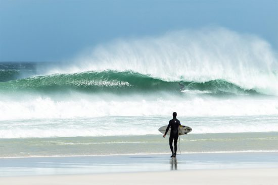 surfer walking on the beach at noordhoek, cape town, whilst another surfer gets barrelled on a wave
